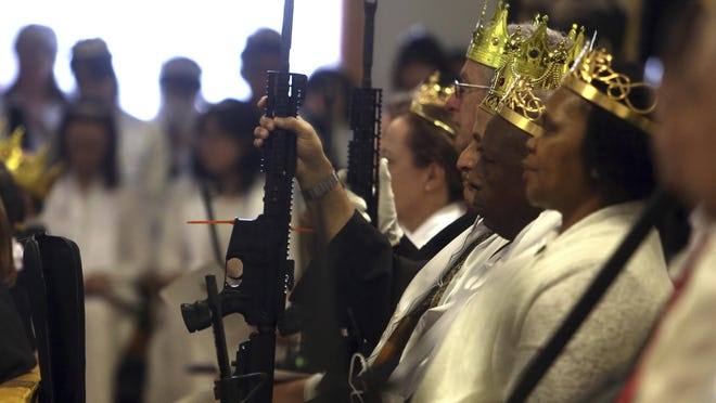 Worshippers hold unloaded weapons at the World Peace and Unification Sanctuary, Wednesday Feb. 28, 2018 in Newfoundland, Pa. Worshippers clutching AR-15 rifles participated in a commitment ceremony at the Pennsylvania-based church.The event Wednesday morning led a nearby school to cancel classes for the day. The church's leader, the Rev. Sean Moon, said in a prayer that God gave people the right to bear arms. (AP Photo/Jacqueline Larma)