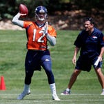 Denver Broncos rookie quarterback Paxton Lynch, front, throws a pass as quarterbacks coach Greg Knapp looks on during NFL football practice Tuesday, May 24, 2016, at the team's headquarters in Englewood, Colo. (AP Photo/David Zalubowski)