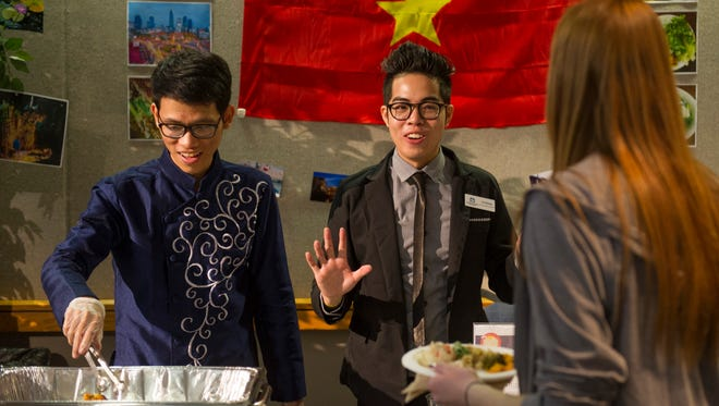 University of Southern Indiana students, Minh Nguyen, left, and Loc Duong, represent the country of Vietnam and serve up Vietnamese pancakes at the International Food Expo at USI's Carter Hall Friday morning.