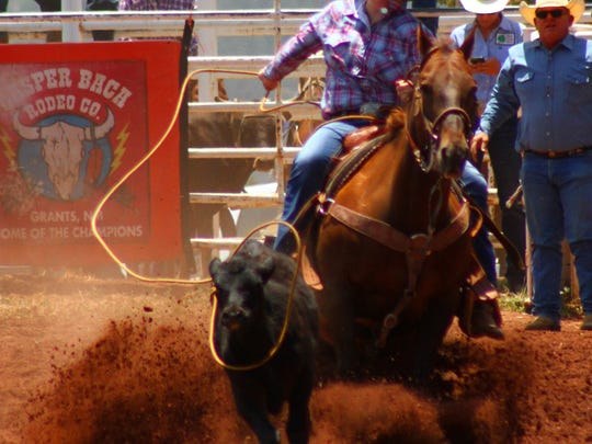 A cowgirl tries to rope a calf during the breakaway roping event.