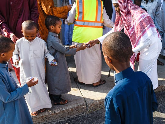 Children receive bags of treats after prayer Friday