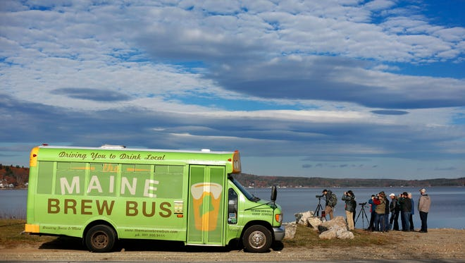 In this Sunday, Nov. 13, 2016 photo a group of birding enthusiasts watch waterfowl on Sabattus Pond in Sabattus, Maine. The Maine Brew Bus tour group combines bird watching and with visits to microbreweries in southern Maine.