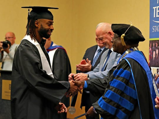MTSU president Sidney McPhee shakes hands with football team member Mike Minter during a special graduation ceremony at the Embassy Suites hotel in Montgomery, Ala., on Dec. 15, 2017.