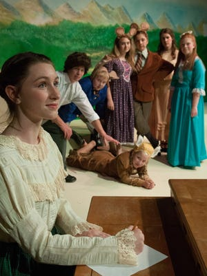 Sarah Byers, foreground, plays the writer Beatrix Potter, with a grooup of characters she created in the background, in DreamWrights' production of 'The Adventures of Peter Rabbit'
