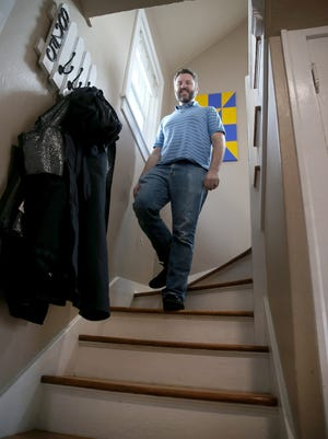 Jeffrey Coughlin walks down the stairs at his Bremerton home built in 1918.