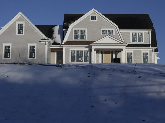 In this Thursday, Feb. 21, 2019 photo a recently constructed home is surrounded by snow in Natick, Mass.
