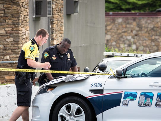 Asheville police officers work the scene of an officer-involved