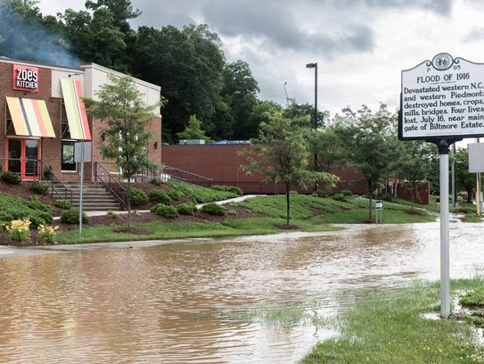 Floodwater covered Swannanoa River Road in Biltmore Village Wednesday morning but newer buildings constructed at higher elevations in compliance with city rules, including the Zoe's Kitchen building at left, escaped damage.