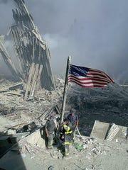 Three New York City firefighters raise an American