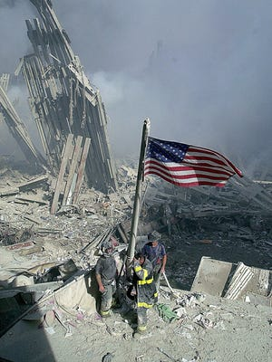 Three New York City firefighters raise an American flag at Ground Zero, site of the World Trade Center, on Sept. 11.