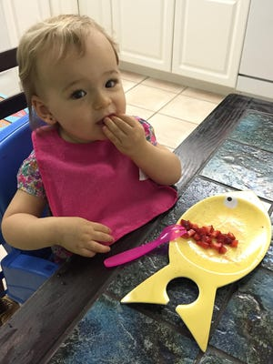 Isabella tests out some strawberries recently at her grandparent's house.