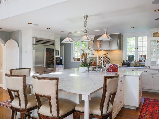 The extended kitchen island is topped with Carrera