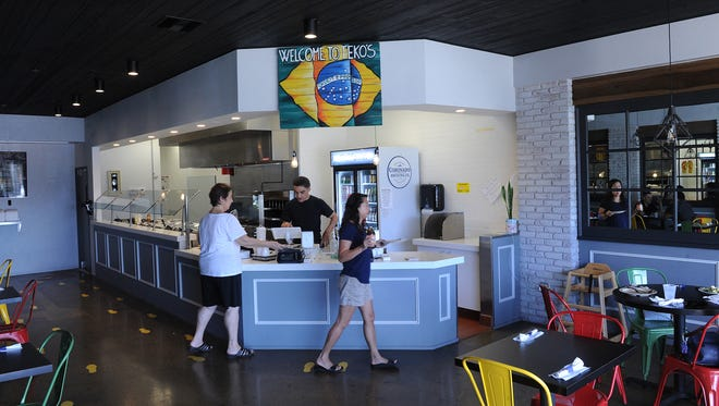 Ross Araujo, owner of Teko's Brazilian Grill, serves customers at the front counter.