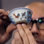"""Sotheby's Nicholas Chow presents the Meiyintang """"Chicken Cup"""" from the Chinese Ming Dynasty in Hong Kong on April 8, 2014."""