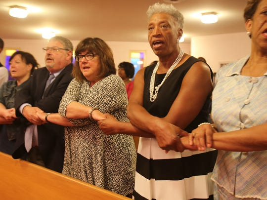 """An interfaith service between  the congregations of Greater New Mt. Moriah Missionary Baptist Church in Detroit and Temple Beth El in Bloomfield Hills  worship and link arms singing """"We Shall Overcome"""" on Sunday."""
