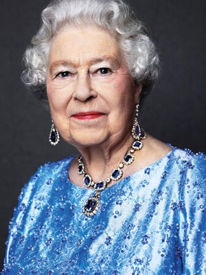 A handout picture released by Buckingham Palace on Feb. 6, 2017 and taken in 2014 by British photographer David Bailey shows the queen wearing a set of sapphire jewelry given to her by King George VI as a wedding gift.