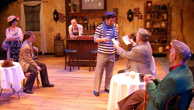 """Picasso (Nick Yocum) has his work appraised by art dealer Sagot (Lindel Salow) in Open Book Theatre's production of """"Picasso at the Lapin Agile.""""  From left:  Allison Megroet, Alexander Sloan, Joshua Brown, Yocum, Salow and Dennis Kleinsmith."""