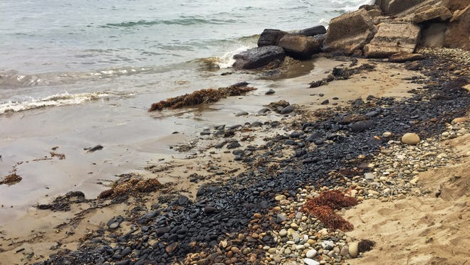 This photo provided by KEYT-TV shows an oily substance that washed onto the beach at Summerland, Calif., south of Santa Barbara on Friday, Aug. 21, 2015. Santa Barbara County health officials at first just warned beachgoers to stay away from the tar balls covering the sand, but after finding more liquid oil, officials decided Friday afternoon to shut it down entirely. (John Palminteri/KEYT-TV via AP) MANDATORY CREDIT: JOHN PALMINTERI/KEYT-TV