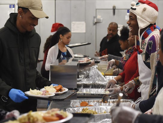 Volunteers laugh while serving food at the annual Eileen