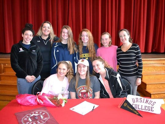 Allie Thomas (center) with some of Ursuline's Swim Team after signing her letter of intent to swim at Ursinus College.