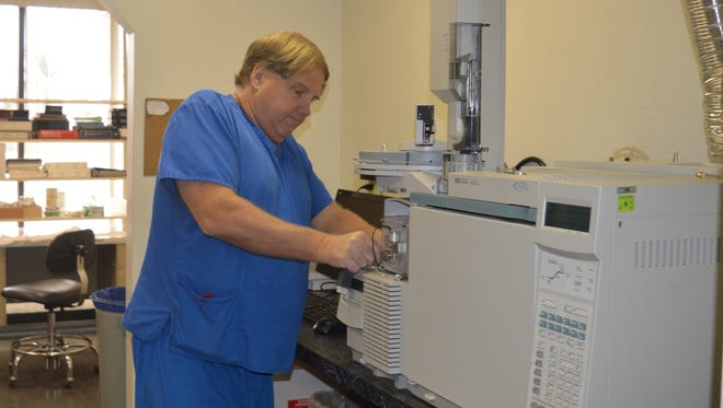 Stephen Comstock, lead toxicologist, works on a machine at the Mineral King Lab lobby.  The lab is reopening on Monday.