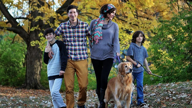 This November  2015 photo provided by Susan Osborne shows Daniel Heumann, 10, with his parents Micah and Sara Heumann and brother Asher, 7. Daniel, was born a girl and named Naima, but has identified as a boy ever since he knew about gender, Micah Heumann said.  Young transgender children allowed to live openly as the gender they identify with fared as well psychologically as other kids in a small study that suggests parental support may be the key.