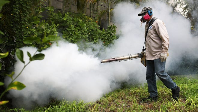 Carlos Varas, a Miami-Dade County mosquito control inspector, sprays pesticide to kill mosquitos in the Miami Beach neighborhood on Aug. 24, 2016, as the county fights to control a Zika virus outbreak.