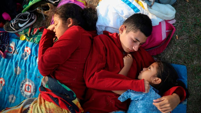 "Zelaya siblings from El Salvador, Nayeli, right;  Anderson, center; and Daniela, huddle together April 4, 2018, on a soccer field at a sports club in Matias Romero, Oaxaca state in Mexico, where Central American migrants traveling with the annual ""Stations of the Cross"" caravan are camped out. The children's father, Elmer Zelaya, 38, said the family is awaiting temporary transit visas that would allow them to continue to the U.S. border, where they hope to request asylum and join relatives in New York."