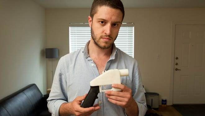 In this May 10, 2013, file photo, Cody Wilson, the founder of Defense Distributed, shows a plastic handgun made on a 3D-printer at his home in Austin, Texas.
