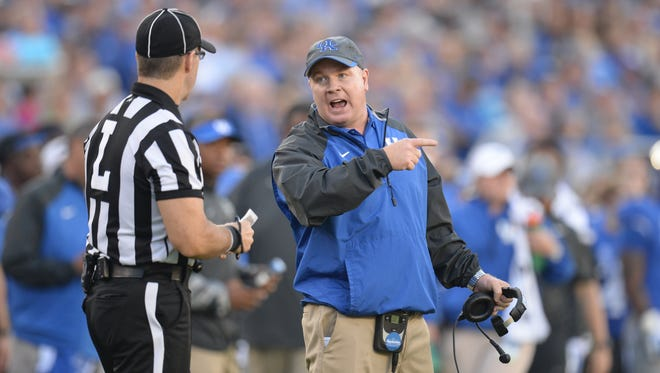 UK head coach Mark Stoops talks with a referee during the second half of the University of Kentucky football game against Mississippi State in Lexington, Ky. Saturday, October 25, 2014.
