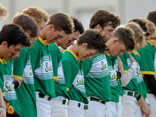 Santa Fe High School baseball players bow their heads