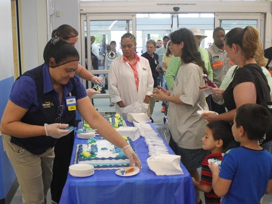 Wal-Mart employee Franci Araujo serves cake to some of the first visitors to the new Village of Estero Wal-Mart on Wednesday.