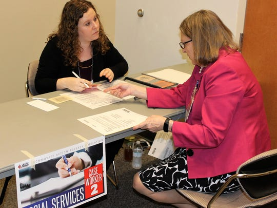 Karlette Peck, right, gets through the lines and application process in order to ask for assistance via social services.