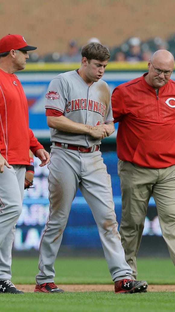 Cincinnati Reds starting pitcher Jon Moscot is escorted off the field by manager Bryan Price, left, and athletic trainer Paul Lessard after being injured in rundown on Detroit Tigers' Anthony Gose during the first inning.