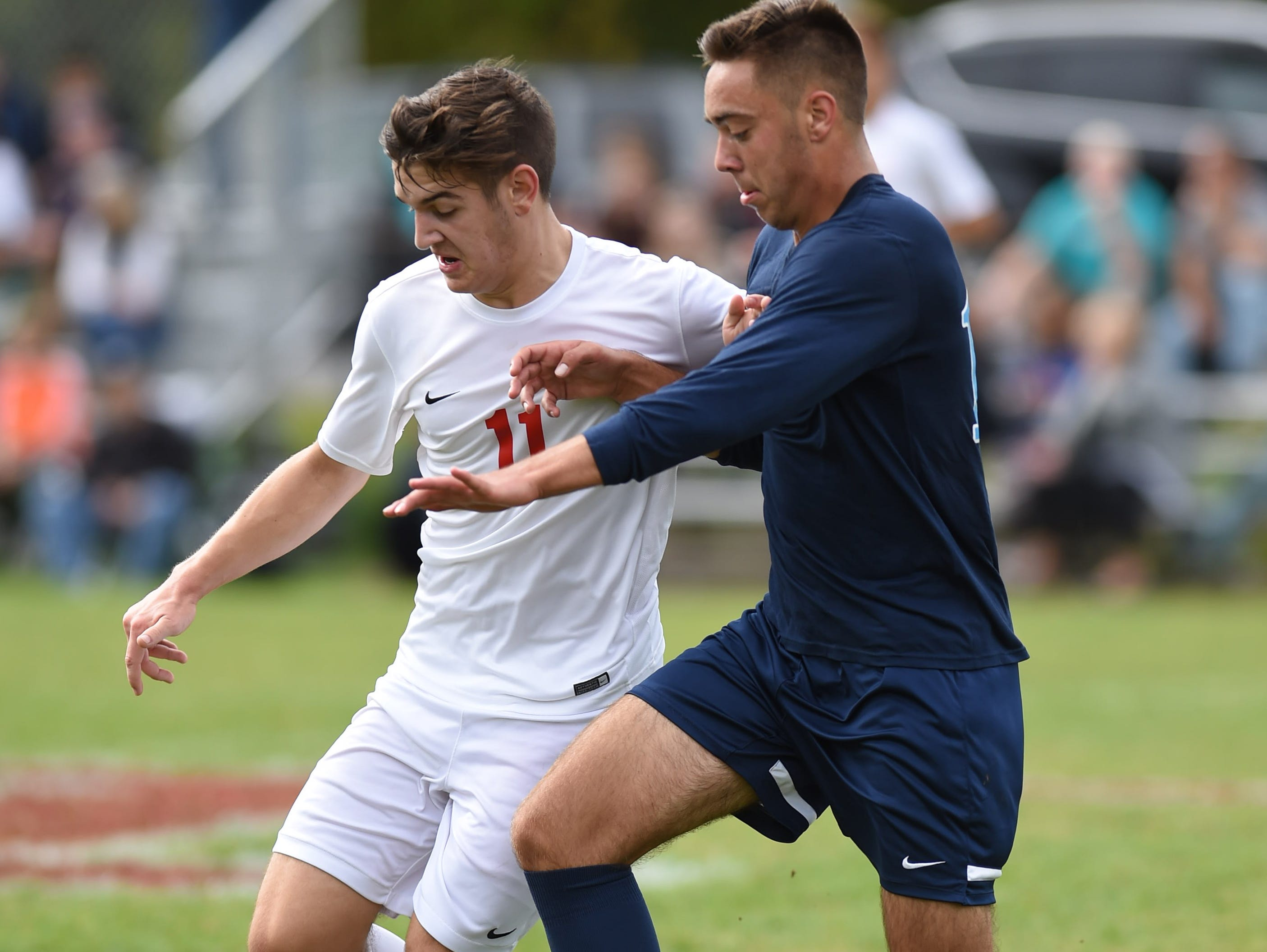 Roy C. Ketcham's Mitchell Kuehner and John Jay's Dylan Tremblay battle for the ball during Saturday's game at Ketcham.