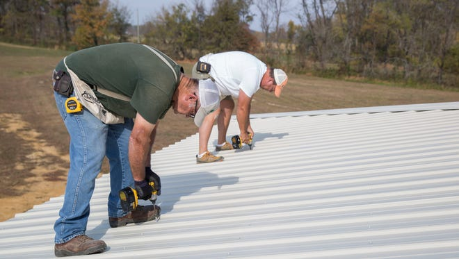 Bill Fulkerson (front) and Tim Johns bolt down the steal to the roof of the new building, The Lodge. They started constructing in May 2015 for the Brain Injury Adventure Camp in Robards, Kentucky.