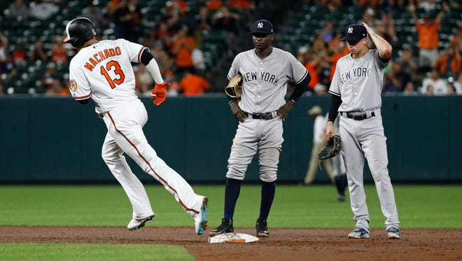 Baltimore Orioles' Manny Machado, left, rounds second base on a two-run home run past New York Yankees shortstop Didi Gregorius, center, and second baseman Neil Walker in the seventh inning of a baseball game, Tuesday, July 10, 2018, in Baltimore. Baltimore won 6-5.