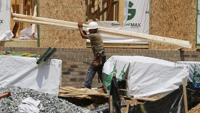 In this photo taken June 8, 2015, a worker carries a load of lumber at a new home construction site in Mechanicsville, Va. The Commerce Department reports on home construction during June on Friday, July 17, 2015.