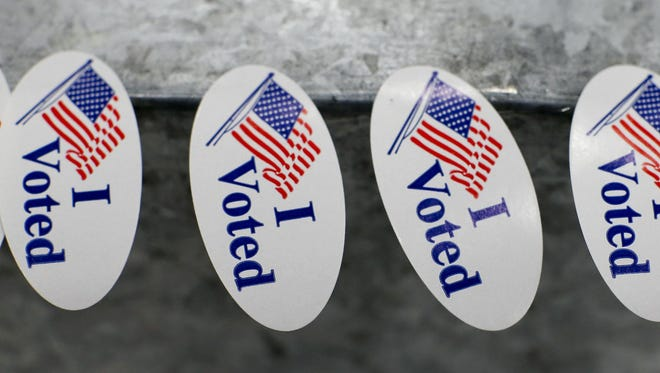 """""""I voted"""" stickers sit on a ballot box waiting to be picked by a voter."""