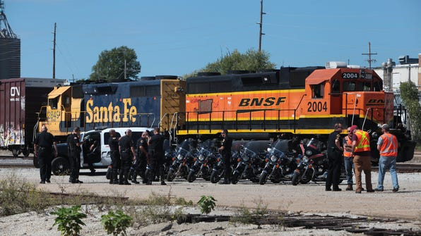 Springfield police officers gather in front of train engines west of Main Avenue on Tuesday. Law enforcement agencies partnered with BNSF Railway officers to promote rail safety education.