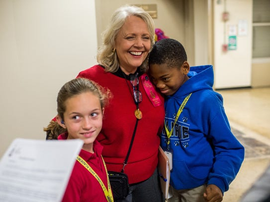 Gayle Abshire, a speech therapist, hugs students after