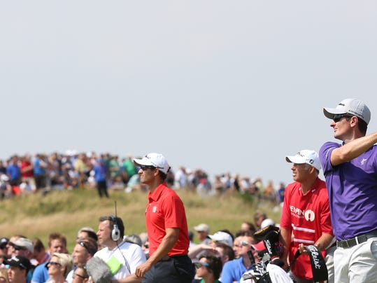 Justin Rose of England plays a shot off the 9th tee as Adam Scott of Australia and his caddie Steve Williams look on during the second day of the British Open Golf championship at the Royal Liverpool golf club, Hoylake, England, Friday July 18, 2014. (AP Photo/Scott Heppell)