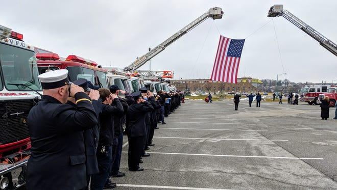 Firefighters salute as the 20-foot-by-40-foot flag is raised between arched ladder trucks ahead of Wednesday's memorial service for two York firefighters who died in the line of duty.