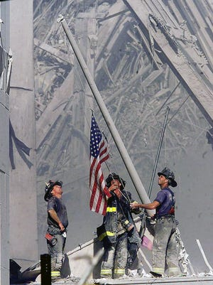 Brooklyn firefighters George Johnson, left, of ladder 157, Dan McWilliams, center, of ladder 157, and Billy Eisengrein, right, of Rescue 2, raise a flag at the World Trade Center in New York, in this Sept. 11, 2001.
