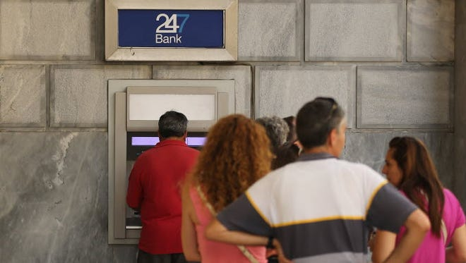 People continue to line up at cash machines on July 13, 2015, in Athens.