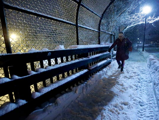 A person walks on a snow-covered sidewalk on a bridge