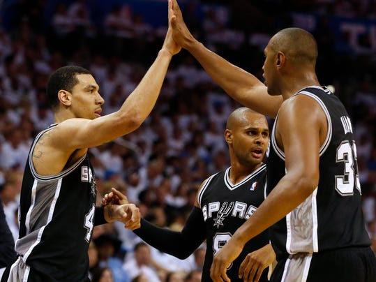 From left, San Antonio Spurs' Danny Green, Patty Mills, and Boris Diaw celebrate during the second half against the Oklahoma City Thunder in Game 6 of the Western Conference finals NBA basketball playoff series in Oklahoma City, Saturday, May 31, 2014. (AP Photo/Sue Ogrocki)