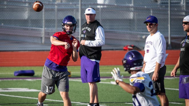 New Blue Springs football head coach David White, center, watches his players go through a passing drill in Monday morning's practice at Peve Stadium. Practice for high school fall sports in Missouri got underway Monday as White ran through his first official practice with the Wildcats after replacing longtime coach Kelly Donohoe.
