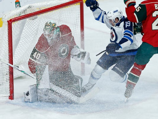 Winnipeg Jets' Nic Petan, right, stirs up the ice as Minnesota Wild goalie Devan Dubnyk gets showered with it during the first period of an NHL hockey game Wednesday, Nov. 23, 2016, in St. Paul, Minn. (AP Photo/Jim Mone)