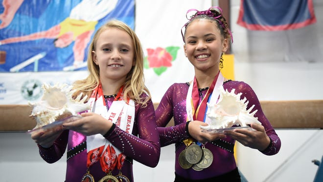 Lillian McClellan, left, and Isabella Kebreau display their multiple awards  at Island Twisters Gymnastics on Feb. 16. McClellan and Isabella each won first place in the all-around in their age divisions, in the annual Aloha Gymfest meet in Kailua, Hawaii, in 2016 and 2015, respectively.
